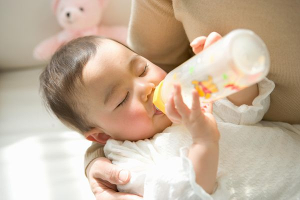Mother holding daughter (6-9 months) drinking from bottle, eyes closed, close-up