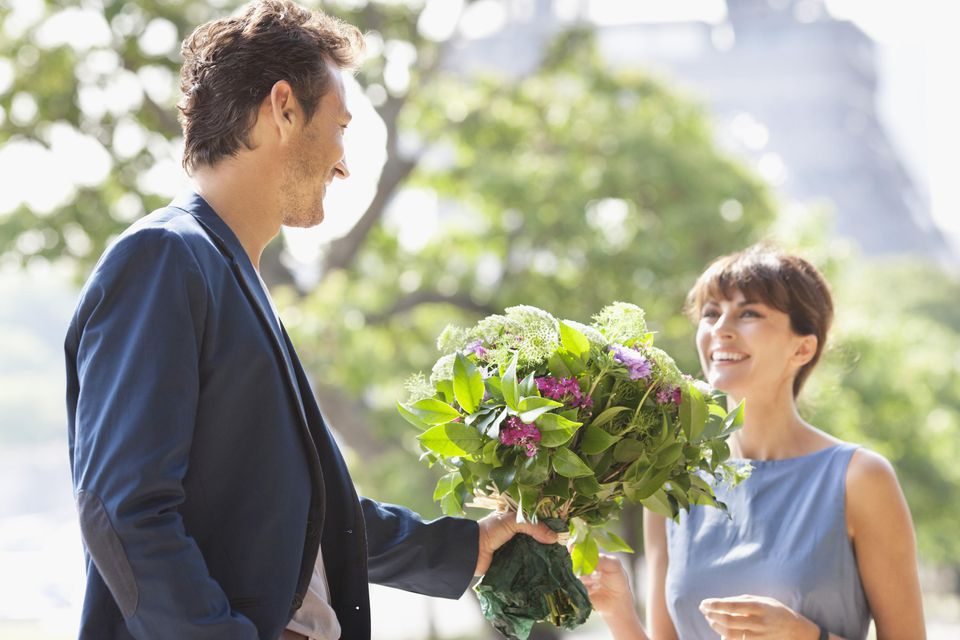 Man giving a bouquet of flowers to a woman