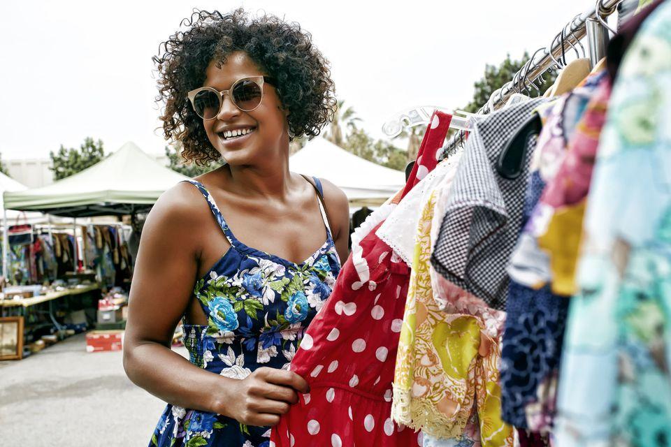 A shopper browses a rack of vintage clothes at an outdoor flea market