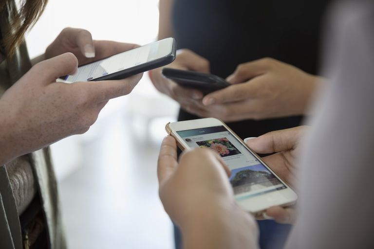 A group of people holding iPhones.