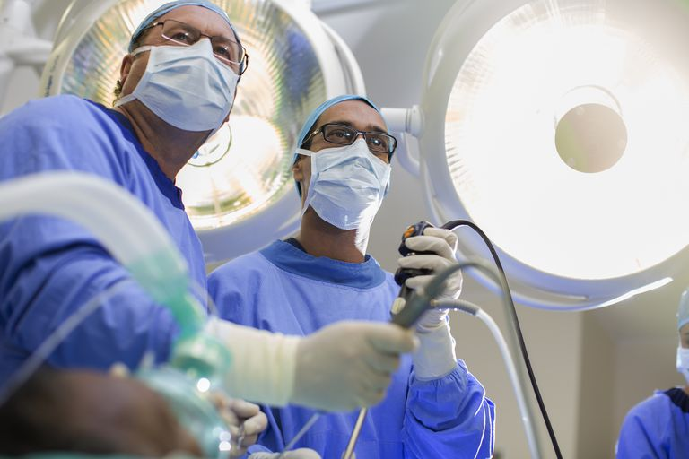 Low angle view of two surgeons holding laparoscopy equipment in operating theater