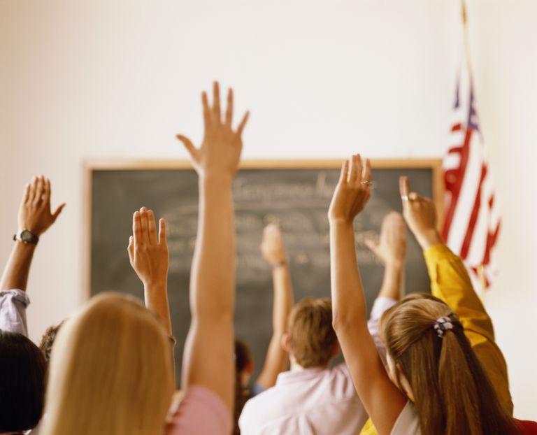 Students raising hands in classroom