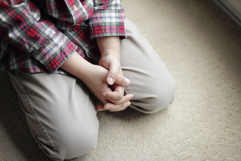 man's hands while kneeling in prayer