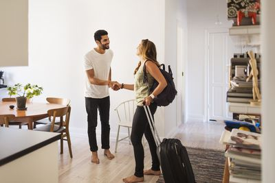Person hosting through home-sharing rental welcoming guest