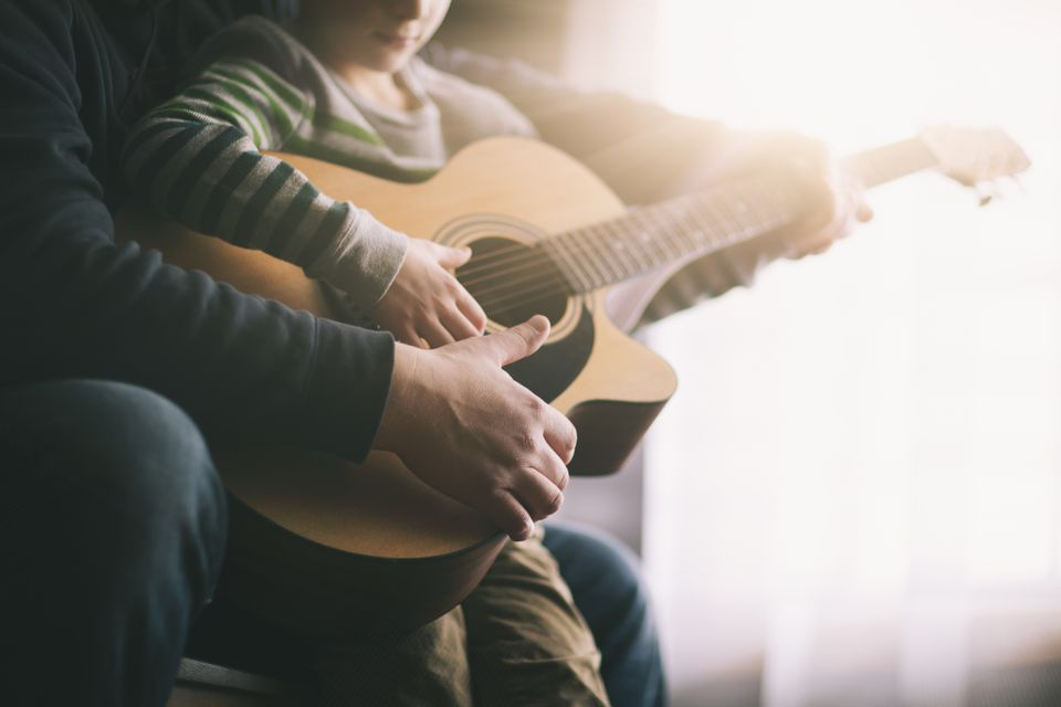 father teaching his son to play guitar