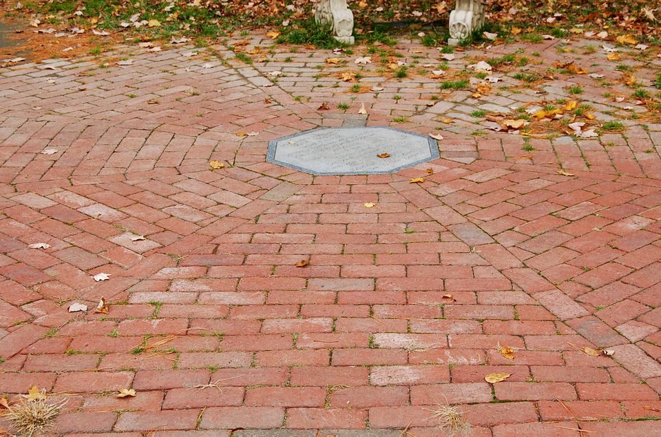 Image of a circular brick patio with a medallion inlay in the center.