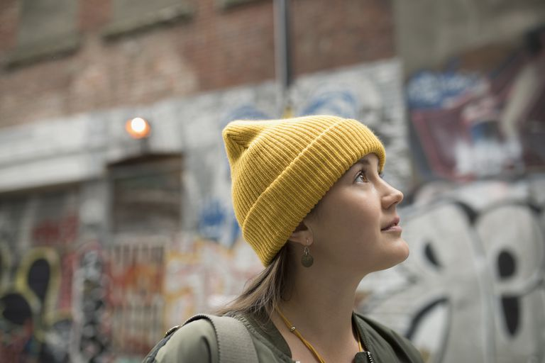 Curious young woman with yellow stocking cap looking up on urban street