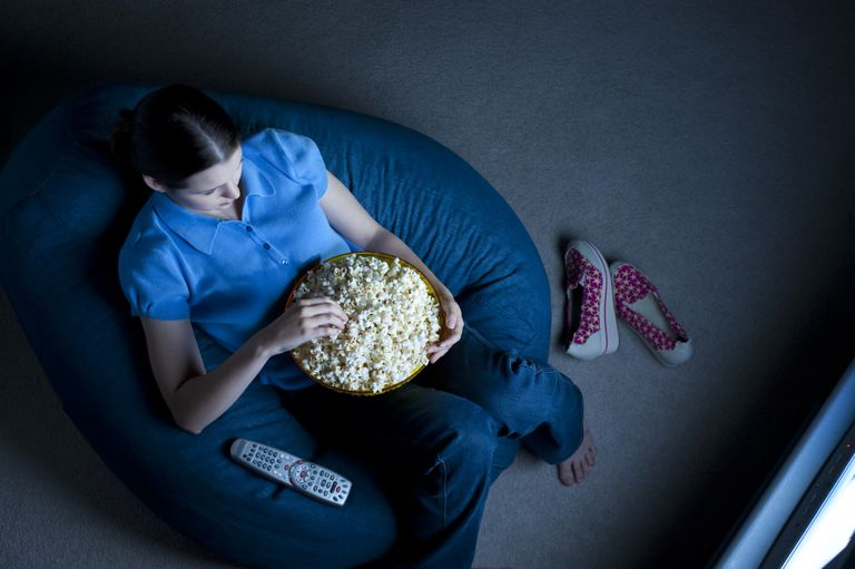 Teenage girl watching tv with popcorn