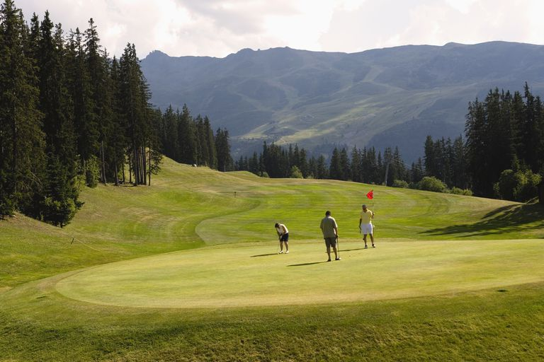 Three golfers on a scenic hole