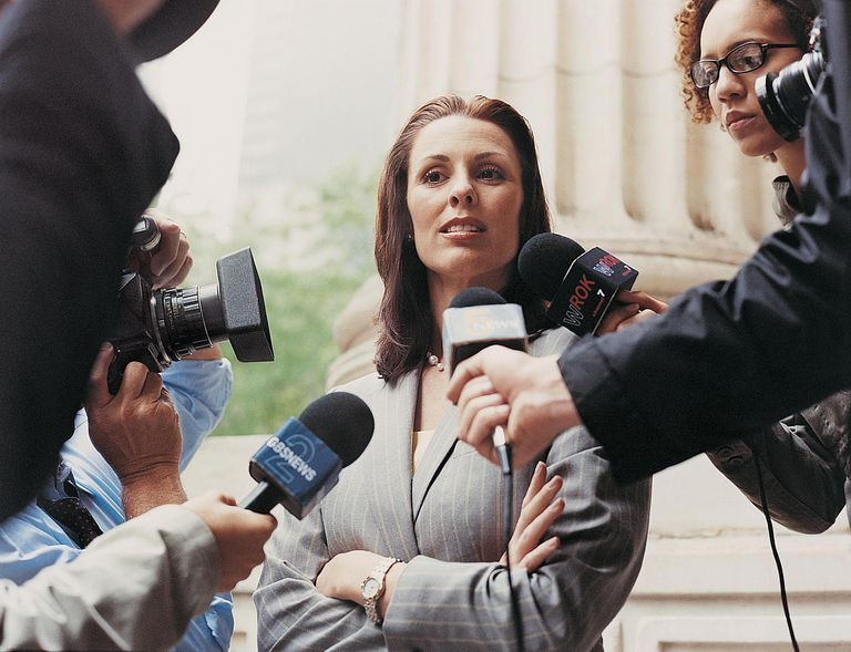 Woman With Her Arms Crossed Being Interview and Photographed by Journalists