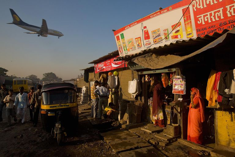 A woman talks on her cell phone as a passenger jet flies over the Jari Mari slum before landing at Mumbai Airport in Mumbai, India. India has historically suffered from significant brain drain but brain gain might be in India's future.
