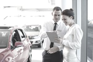 A man and woman looking at a tablet next to a car