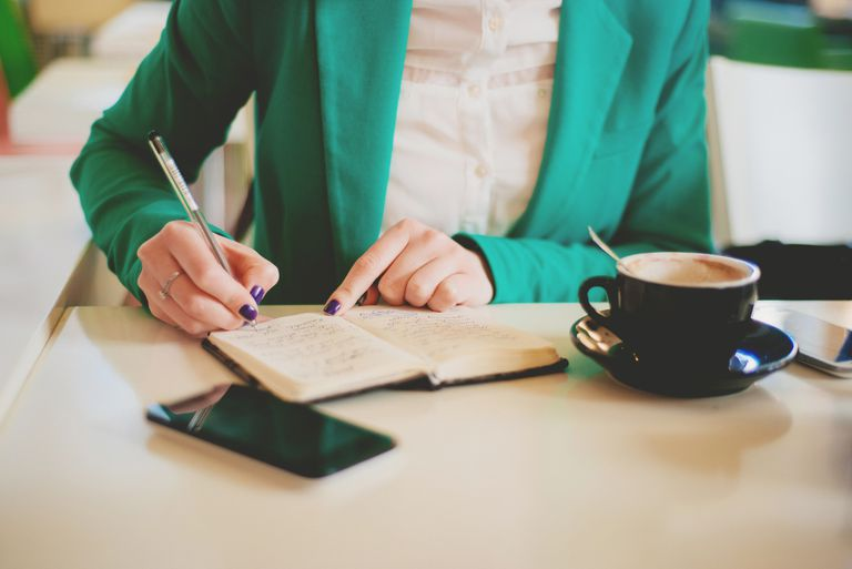 Woman writing list in notebook