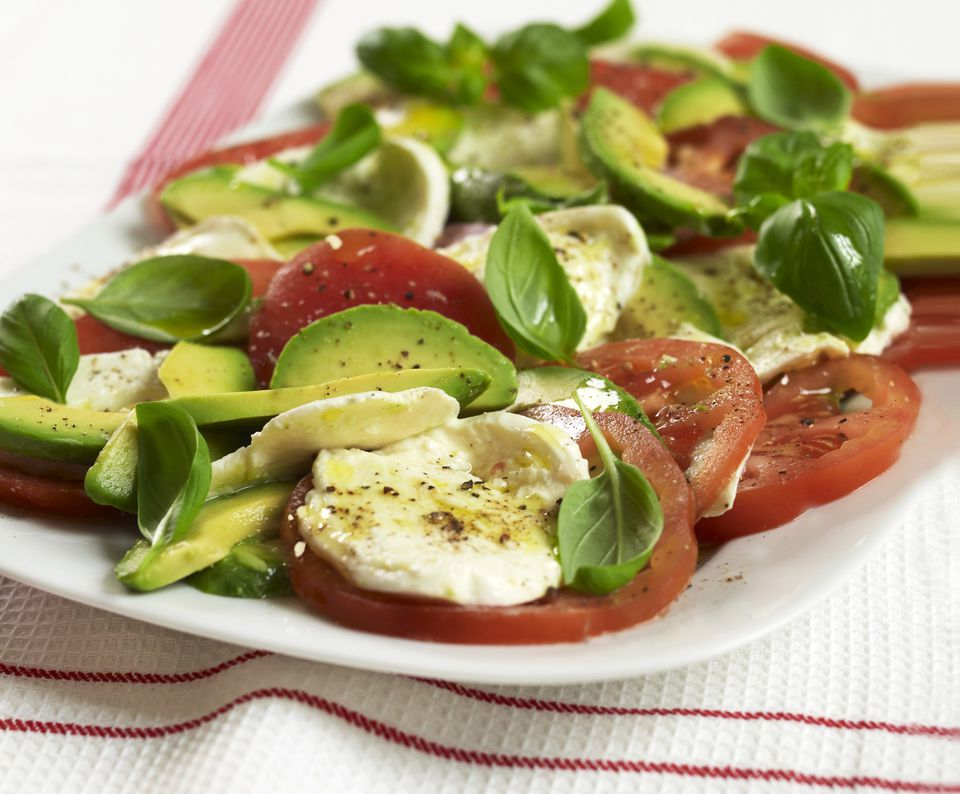 Tricolore avocado caprese salad with mozzarella, tomato and fresh basil