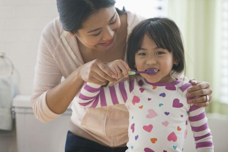 mother helping daughter brush teeth