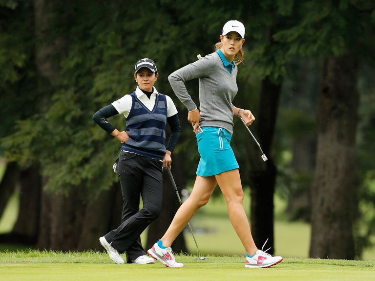 Michelle Wie of the USA (R) and Ai Miyazato of Japan wait on the second green during the third round of the 2013 Lorena Ochoa Invitational