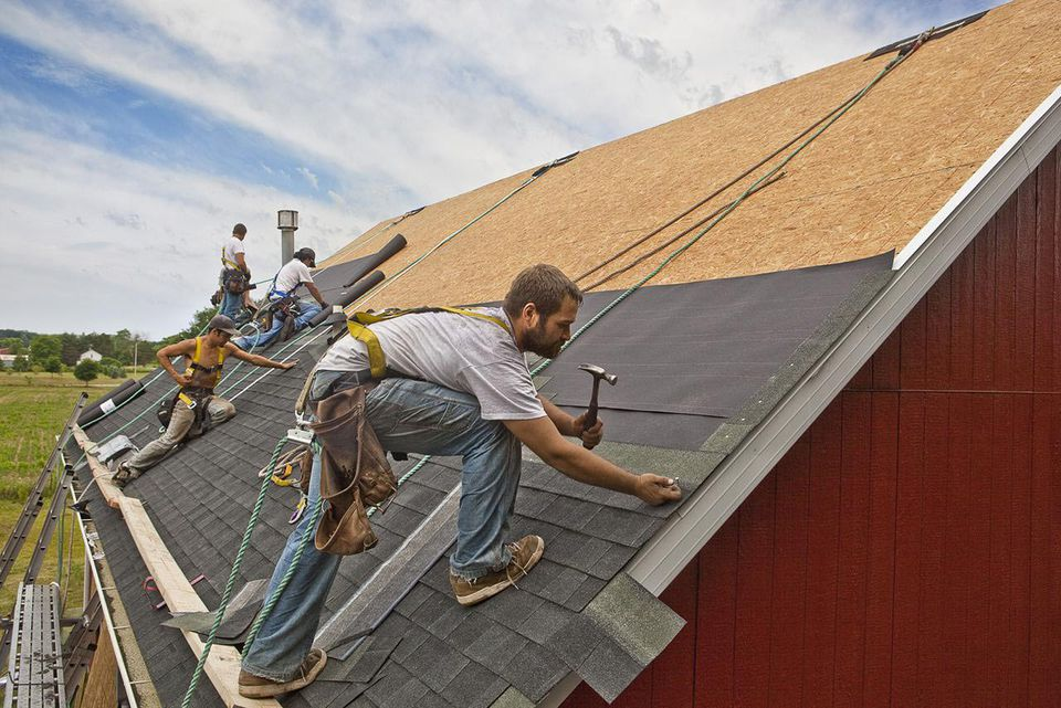 A team of men install waterproofing material and shingles to create a new roof on a rural building.