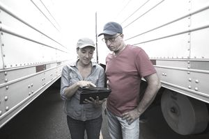 Two drivers looking at electronic tablet