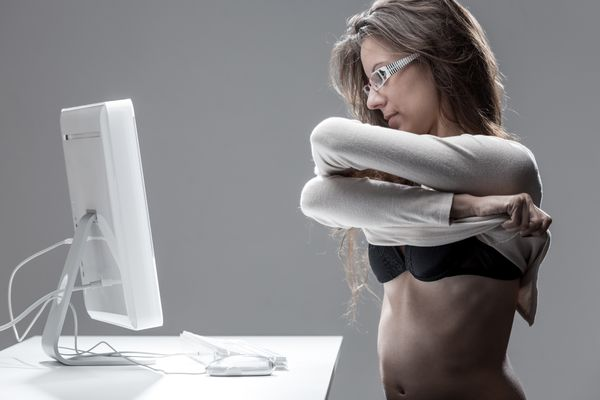 Woman undresses in front of computer
