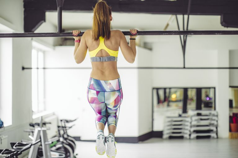 woman doing pull up in a gym