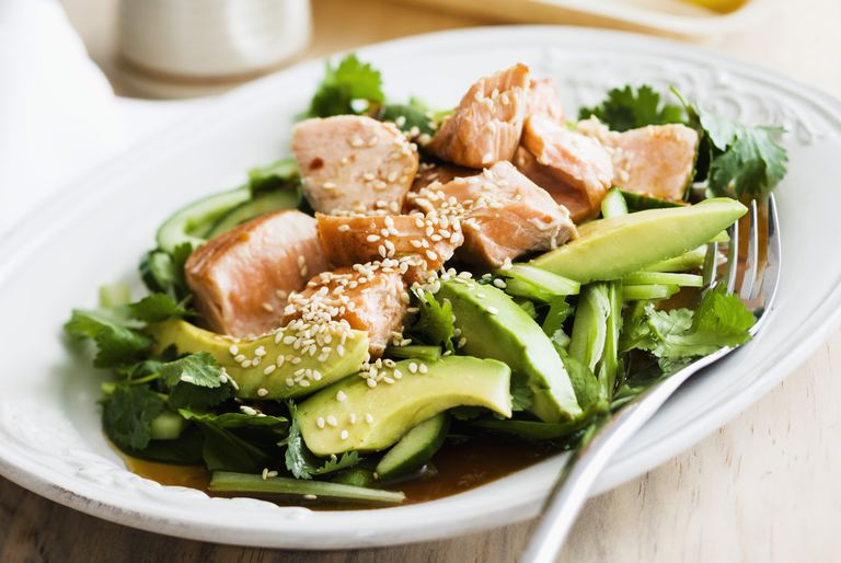 Grilled salmon on an avocado & cucumber salad served in plate