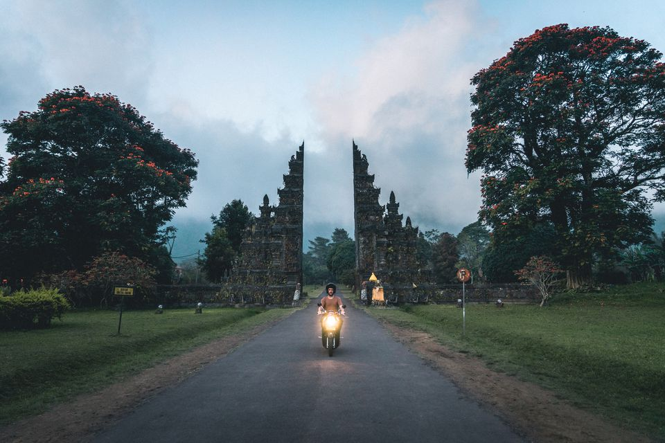 Mid Adult Man Riding Motorcycle On Road Amidst Trees Against Sky