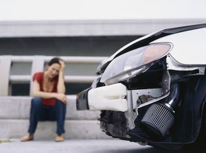 Upset woman sitting near wrecked front of car