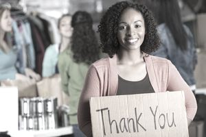 Beautiful black female holds a thank you sign with coworkers in the background