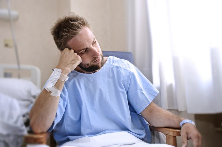 Man patient in hospital room sitting alone in pain sad