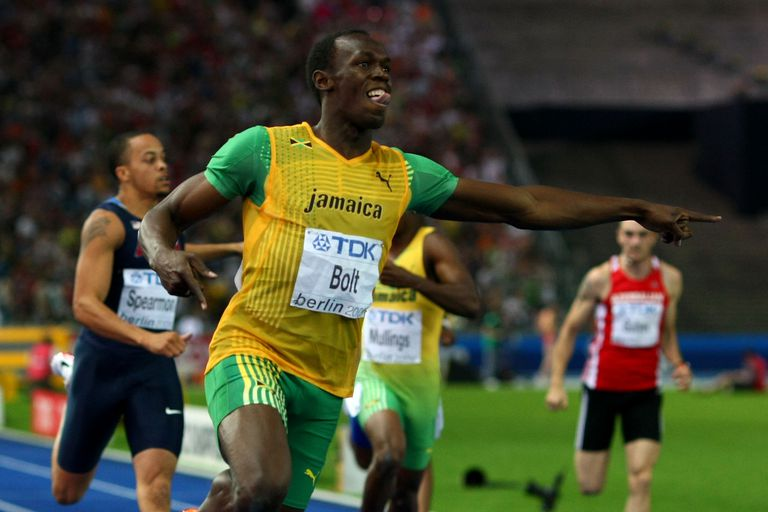 Usain Bolt points to the time clock as he crosses the line in the 2009 World Championship 200-meter final. Bolt finished in a world-record time of 19.19 seconds.