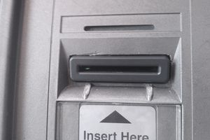A card skimmer inserted in an ATM. Note the damaged plastic and mismatched color