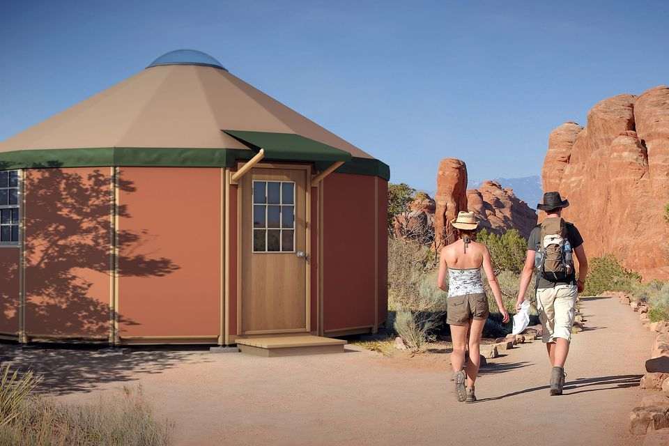 Two hikers next to a Freedom Yurt cabin