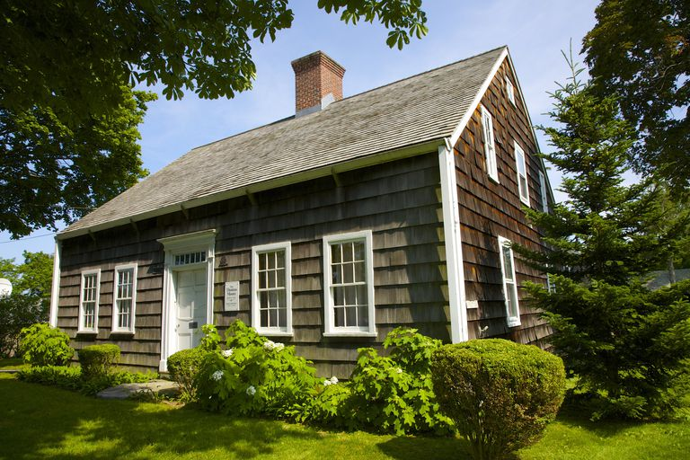 Brown-shingled, center chimney, 6-over-6 double hung windows on each side of central doorway, Cape Cod style 17th century house on Long Island, New York