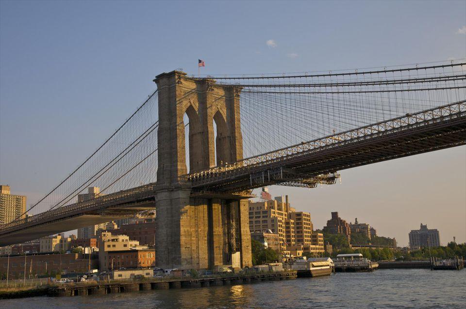 Stone tower of suspension bridge at dusk.