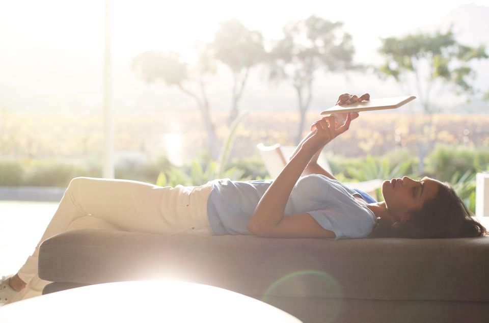 Woman laying on chaise lounge using digital tablet on sunny patio