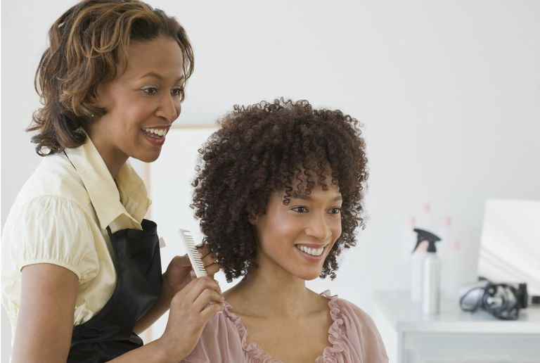 Woman consulting her hairstylist on relaxers vs. texturizers