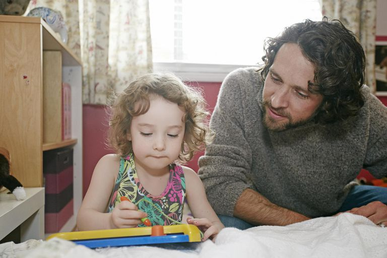 Caucasian father and daughter playing in bedroom