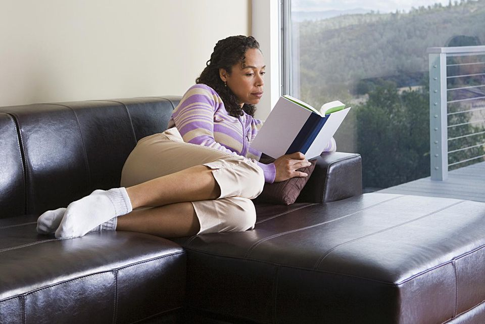Woman reading on a leather couch