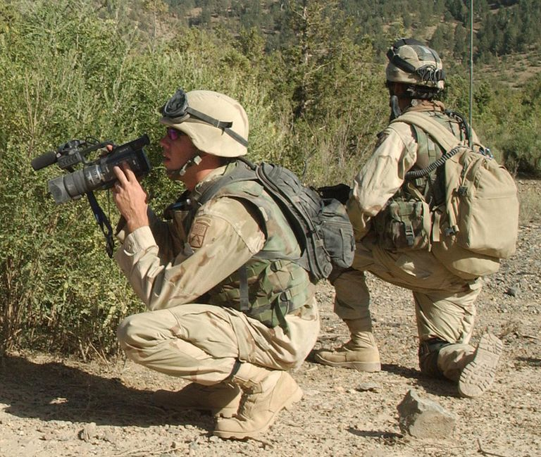 A member of the Signal Corps shoots video of 10th Mountain Division soldiers as they search a mountainside near Shkin Firebase in late 2003.