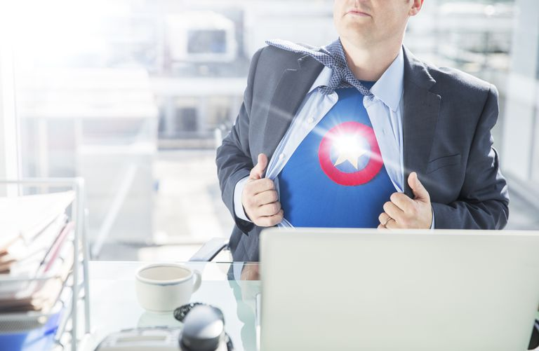 man opening shirt to show superhero costume in front of laptop