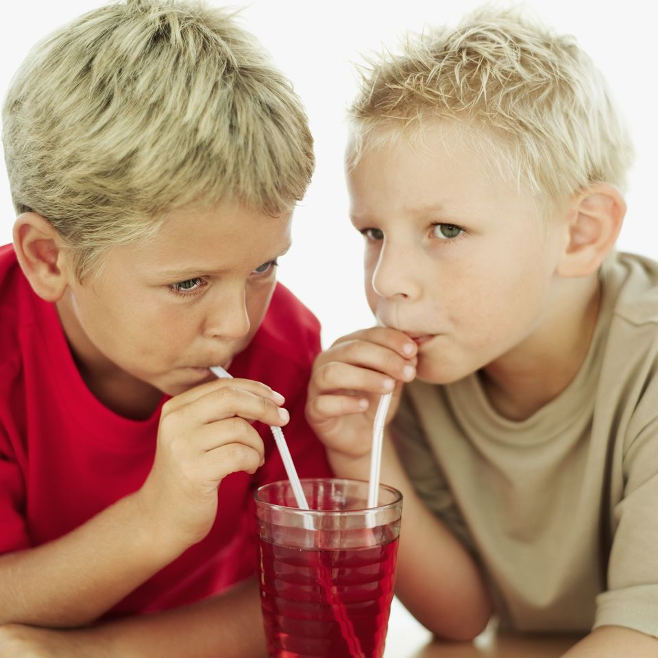 boys drinking red juice with straws