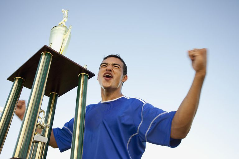 Soccer player cheering next to gold trophy