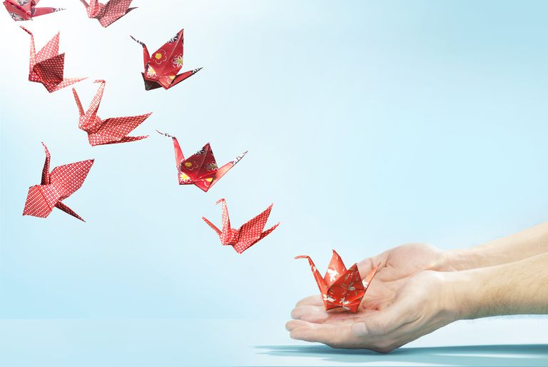Red origami cranes flying away from hands