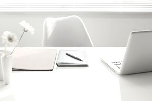 empty office desk with flowers, notebook and laptop on table