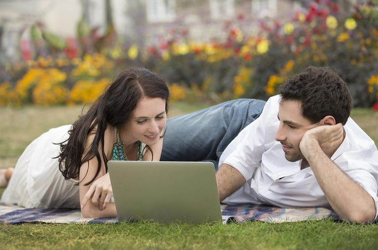 A couple looking at a laptop in a park