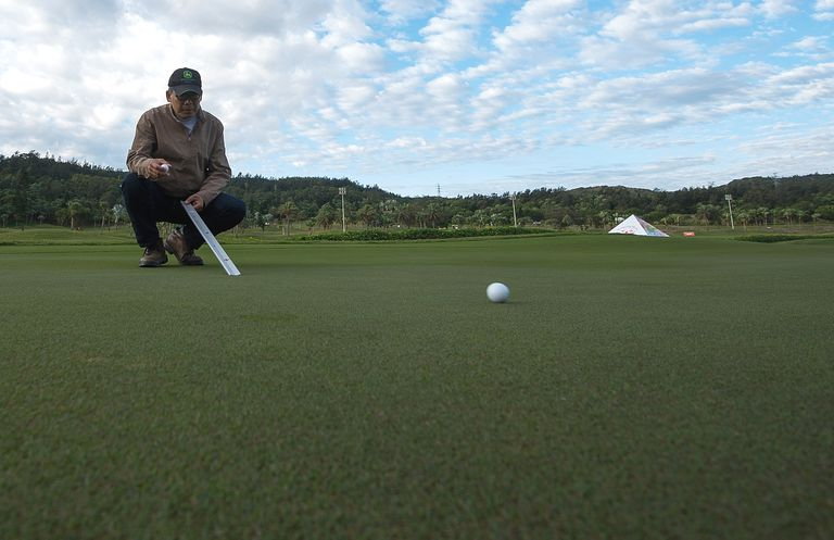 Course superintendent uses a Stimpmeter to measure green speed
