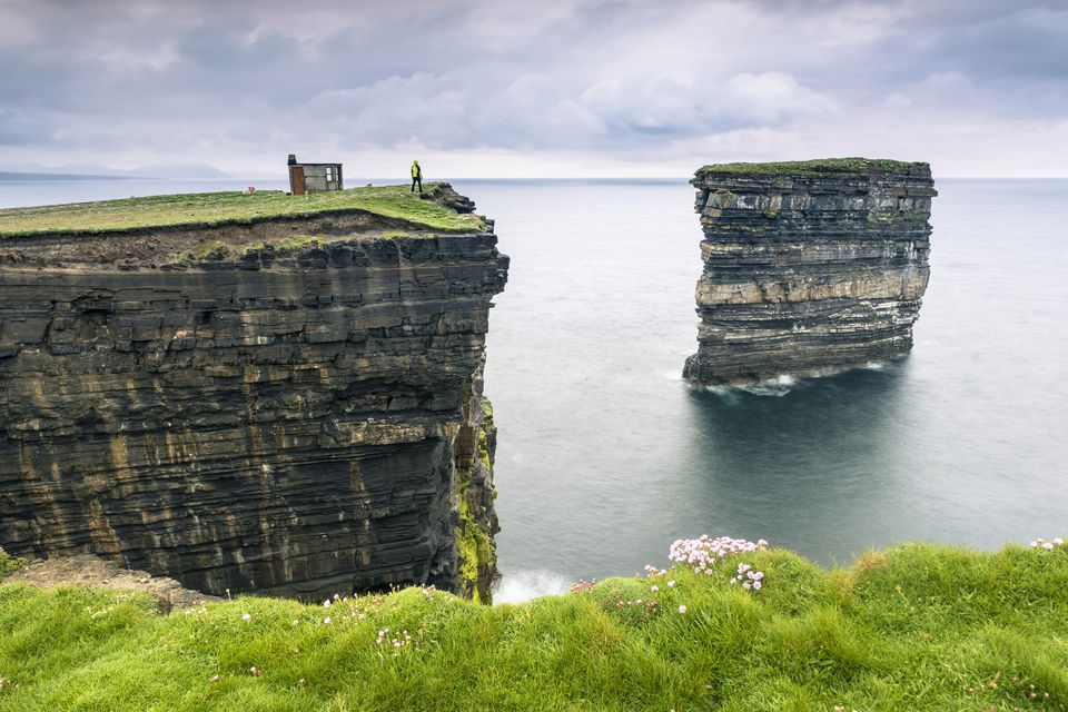 Ireland, Connacht region, County Mayo, Ballycastle, Downpatrick Head, Man watching sea stack from top of cliff