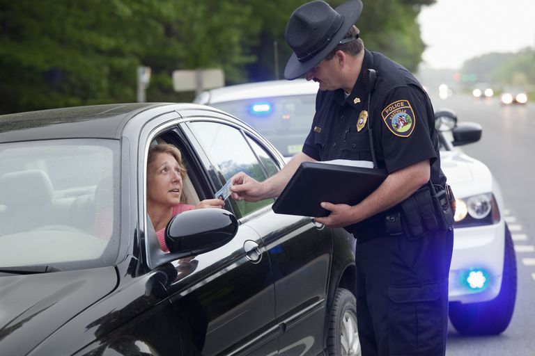 State trooper hands driver a traffic ticket