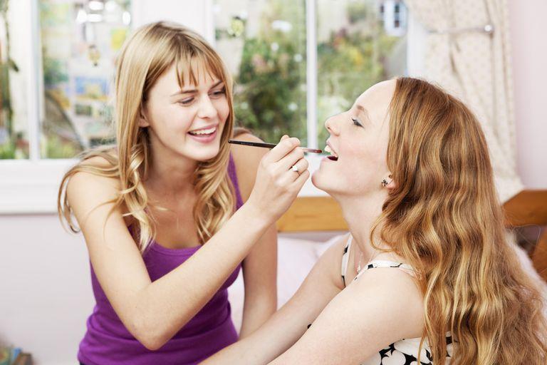 Teenage girl applying makeup to younger sister