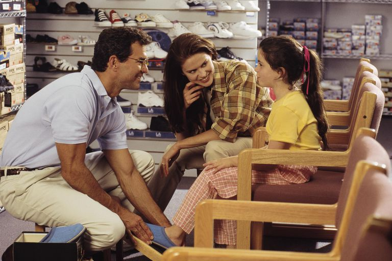 Daughter trying on shoes with mother and salesperson